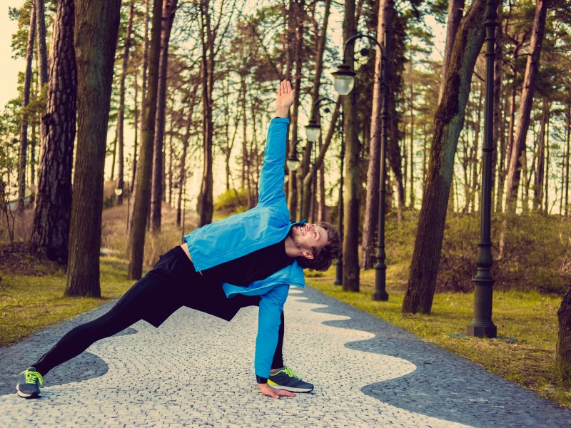 Flexible fitness man in a blue sports jacket exercising outside.