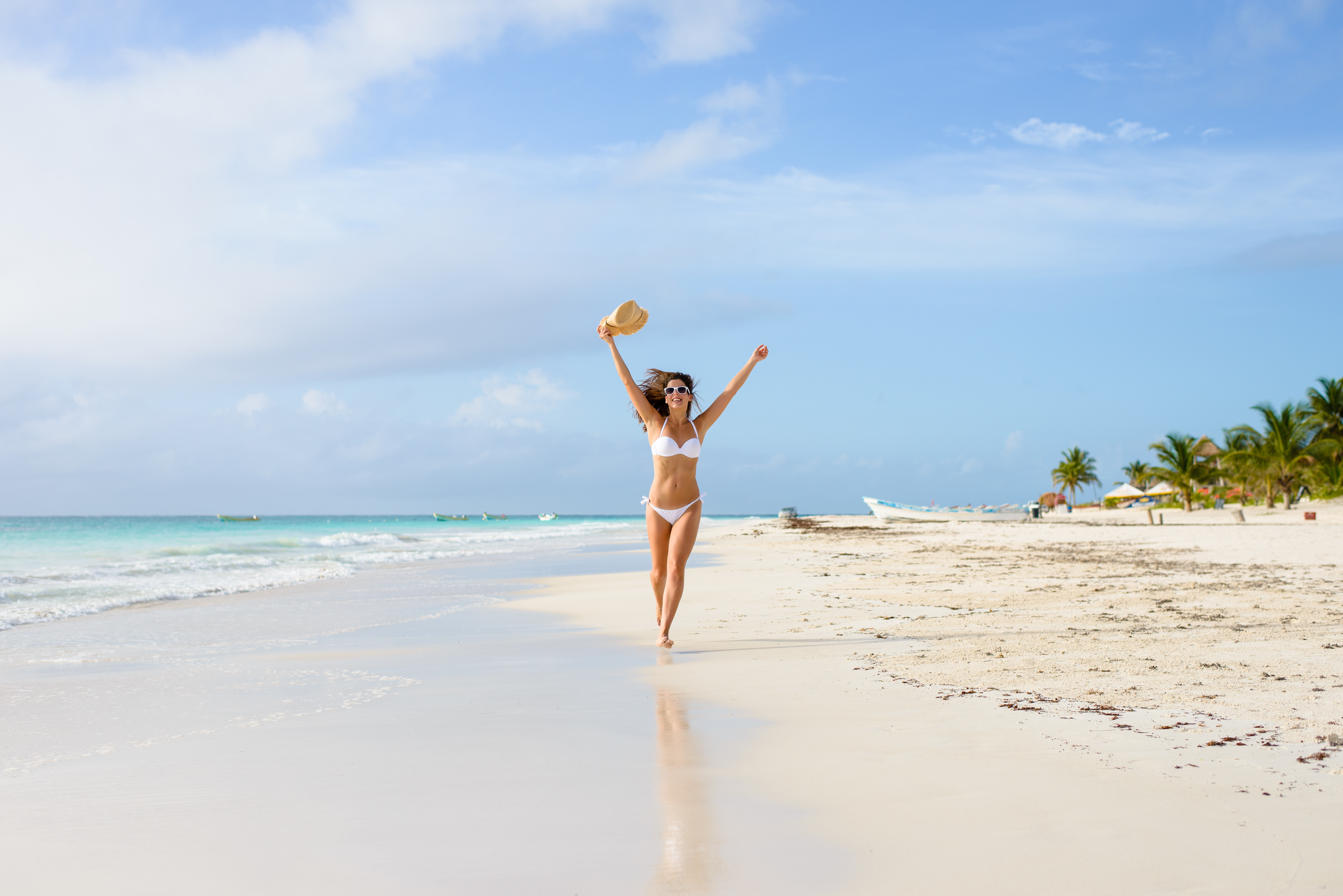 Beautiful joyful woman in white bikini enjoying tropical beach and caribbean summer vacation. Tanned brunette running free by the sea at Playa Paraiso, Riviera Maya, Mexico.