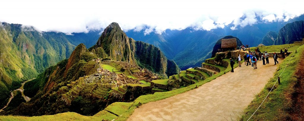 A Landscape Image of Machu Picchu with tourists taking photos.